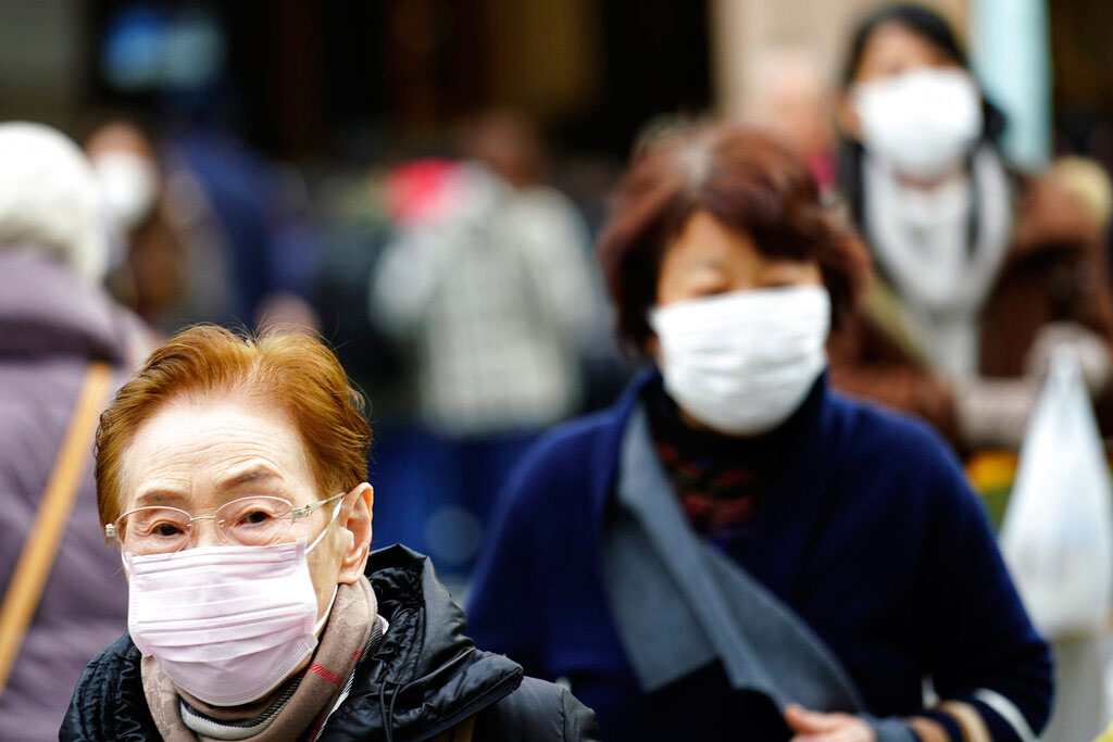 Pedestrians wear protective masks as they walk through a shopping district in Tokyo