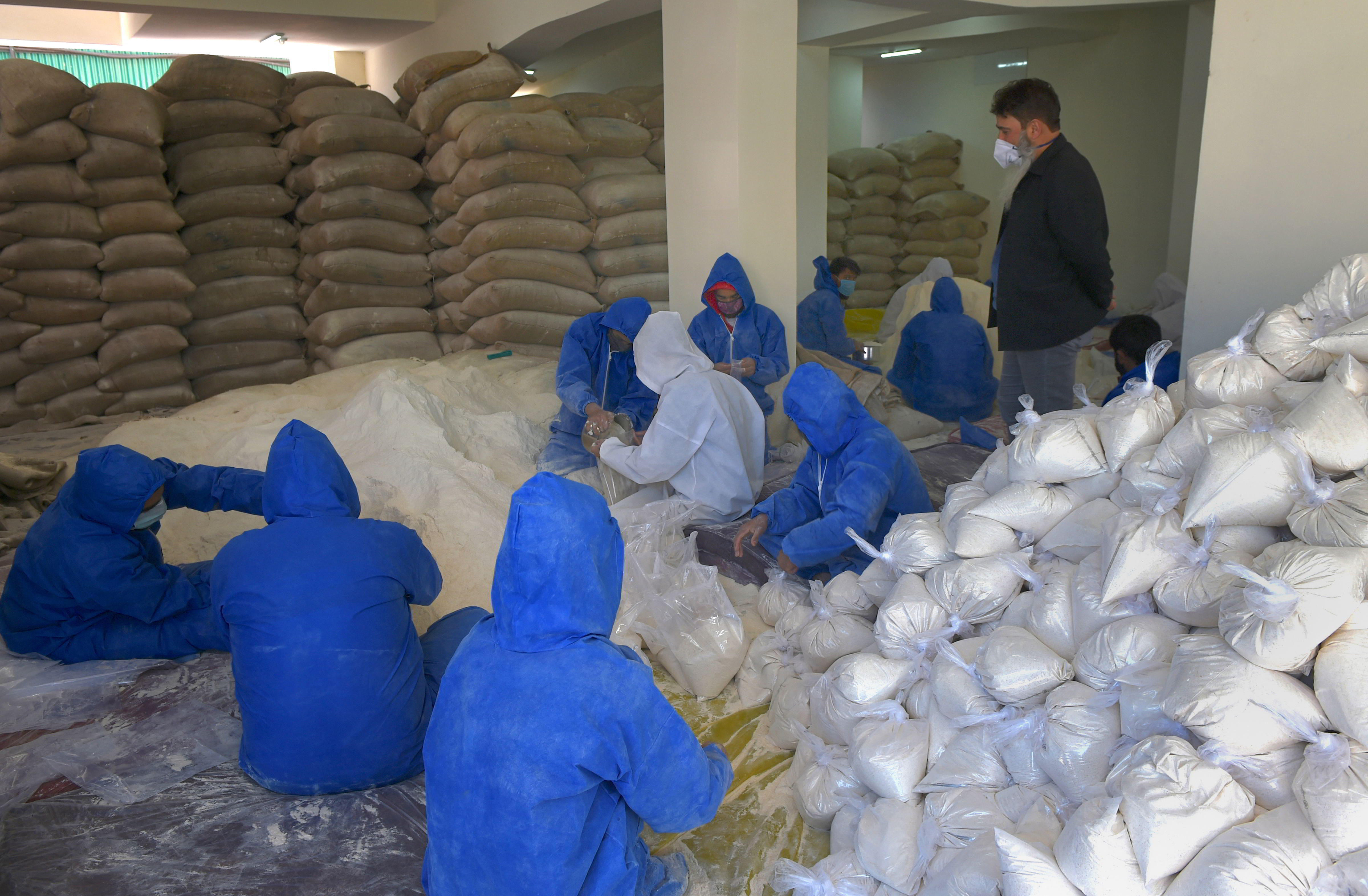 Workers wearing protective suit prepare food packets to distribute among the needy ahead of Ramadan, during the nationwide lockdown to contain the spread of coronavirus, in Srinagar, Tuesday, April 21, 2020