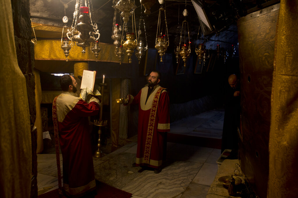 Christian Armenian pray inside the Grotto of the Church of the Nativity, traditionally believed by Christians to be the birthplace of Jesus Christ, in the West Bank city of Bethlehem on Christmas Eve, Tuesday, Dec. 24, 2019.