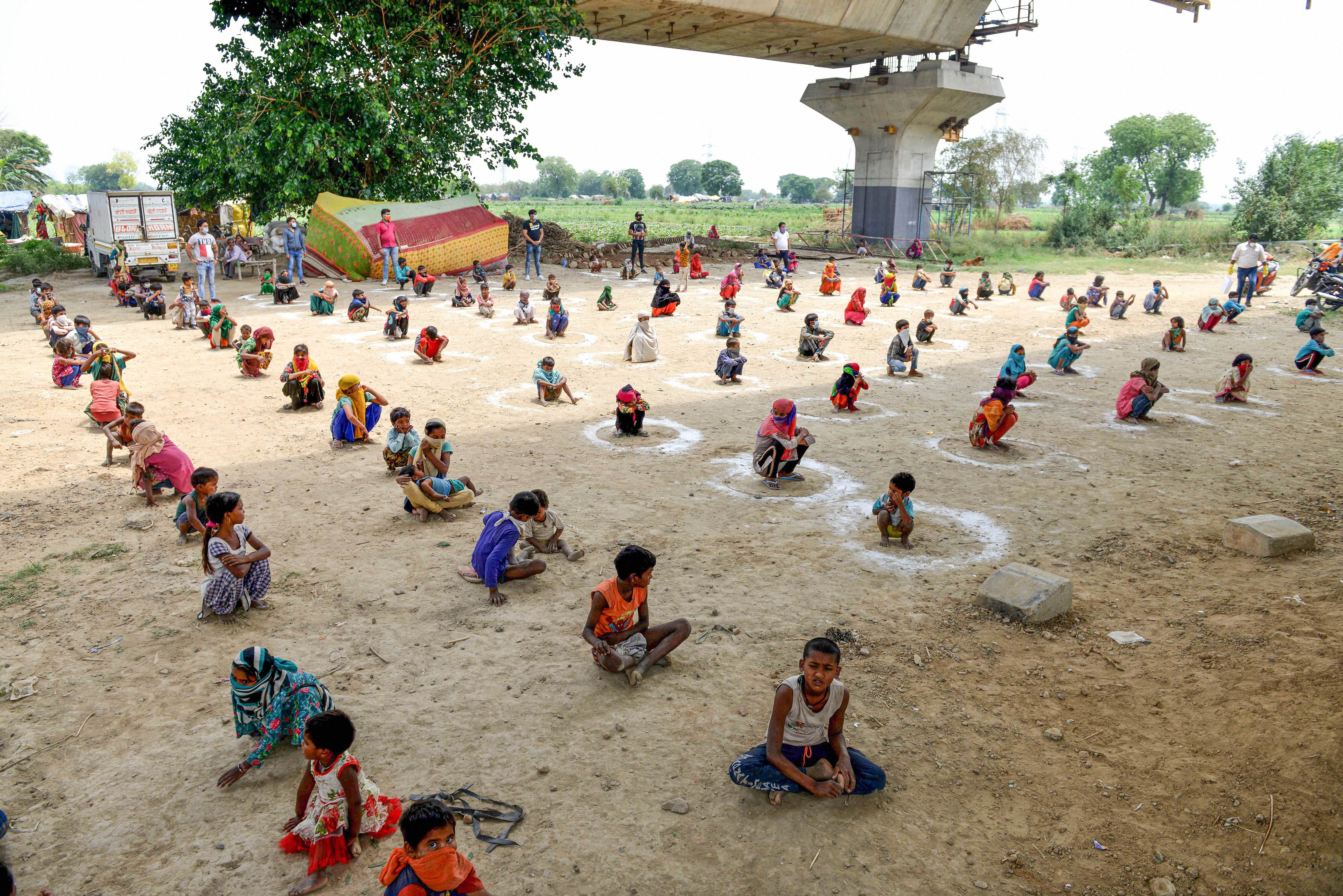 Children sit inside painted circles maintaining social distance during the food distribution by volunteers amid the ongoing nationwide Covid-19 lockdown, in New Delhi, Monday, May 11, 2020