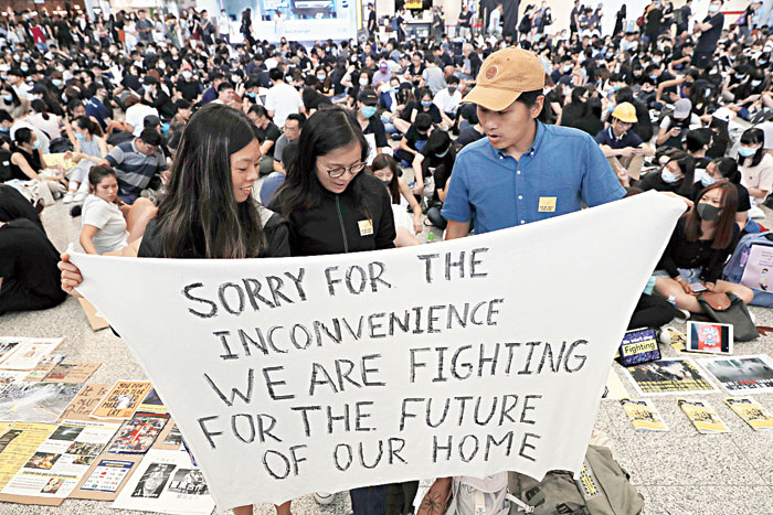 Protesters hold a poster at the Hong Kong airport on Friday