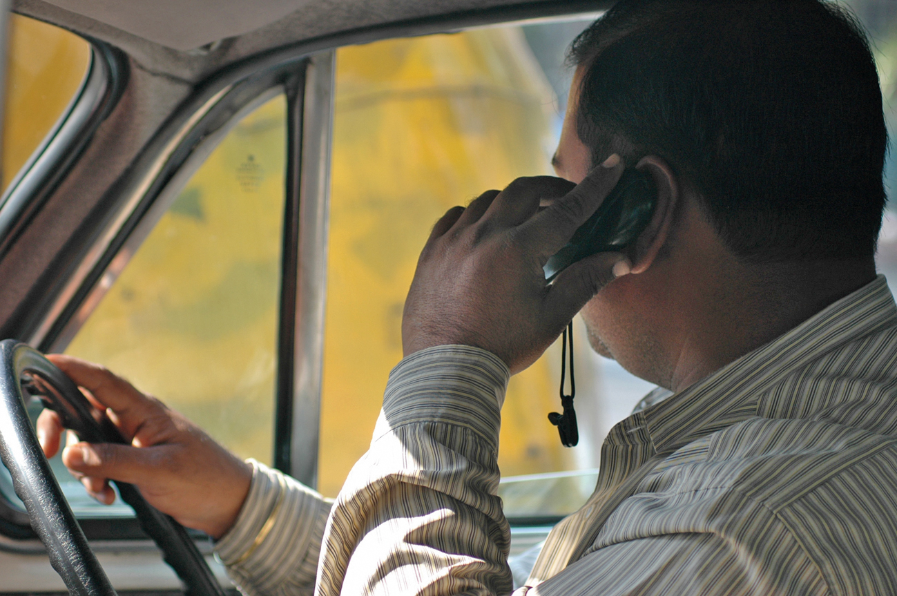 A motorist speaks on his mobile phone while driving