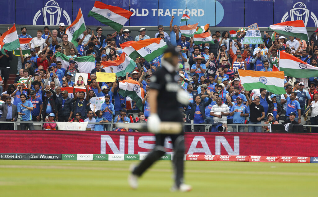 Indian supporters celebrate after New Zealand's Martin Guptill (foreground) was dismissed by Jasprit Bumrah during the cricket World Cup semi-final match at Old Trafford in Manchester, England, on Tuesday, July 9, 2019