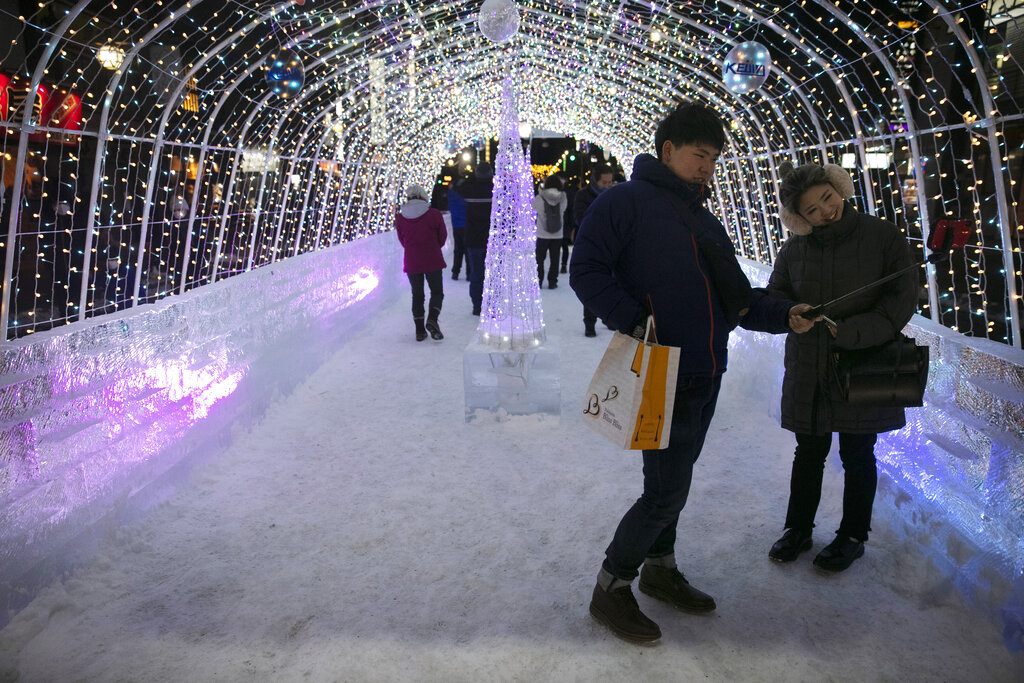 Tourists take a selfie in a tunnel made with ice blocks at the annual Sapporo Snow Festival