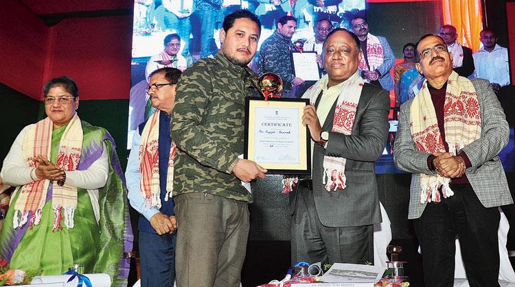 Parimal Suklabaidya awards photographer Rupjyoti Sarma for winning the wildlife photography contest, organised to mark World Wetlands Day, on Sunday