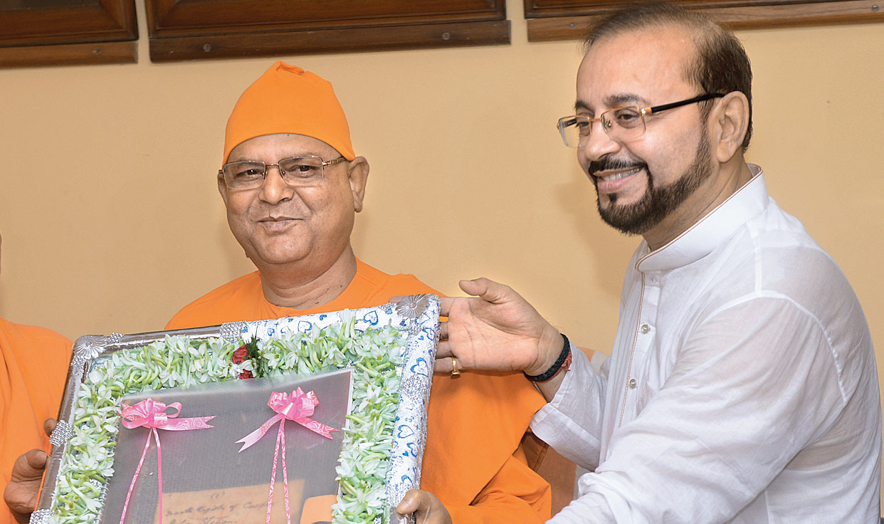 """Deputy mayor of CMC Atin Ghosh hands over a replica of the death register that has an entry in the name of """"Ram Kisto Promohongsa"""" to Swami Suvirananda, the general secretary of Ramakrishna Math and Ramakrishna Mission, on Saturday."""