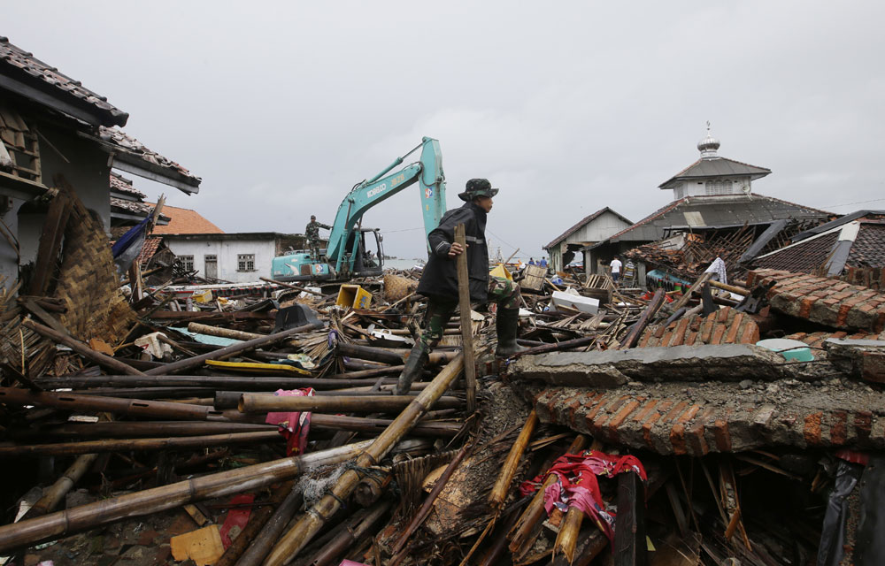 An Indonesian soldier searches for tsunami victims in Sumur, Indonesia on Tuesday, December 25, 2018.