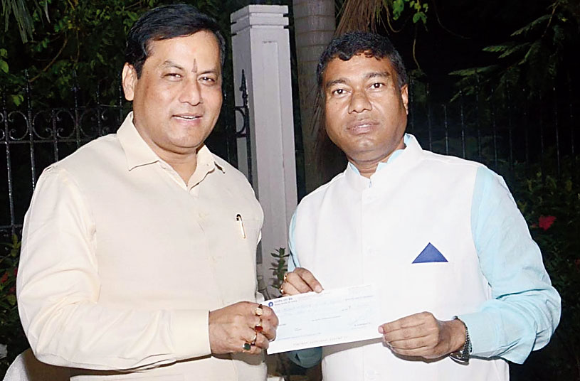 Chief minister Sarbananda Sonowal receives a flood donation cheque from Rameswar Teli in Guwahati.