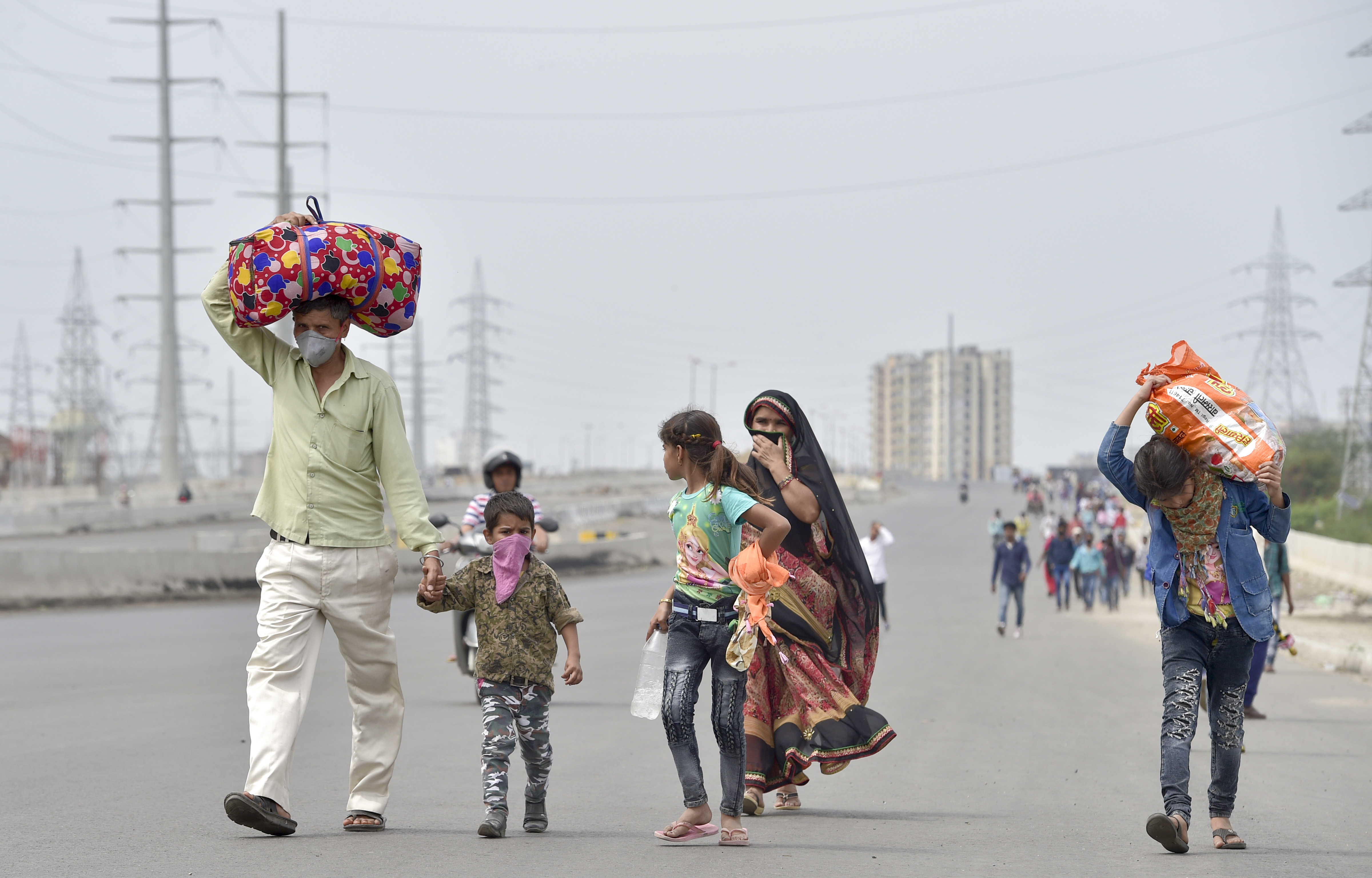 People return to their native place on foot due to absence of any means of transportation during day-2 of a nationwide lockdown, imposed in the wake of coronavirus pandemic, in Ghaziabad, Thursday, March 26, 2020