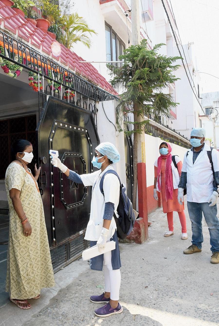 A health worker screens a resident of the novel coronavirus symptoms near Hindpiri in Ranchi on Tuesday.
