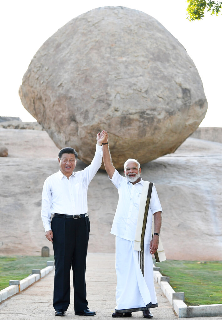 Chinese President Xi Jinping and Prime Minister Narendra Modi raise hands together at Arjuna's Penance in Mamallapuram, India
