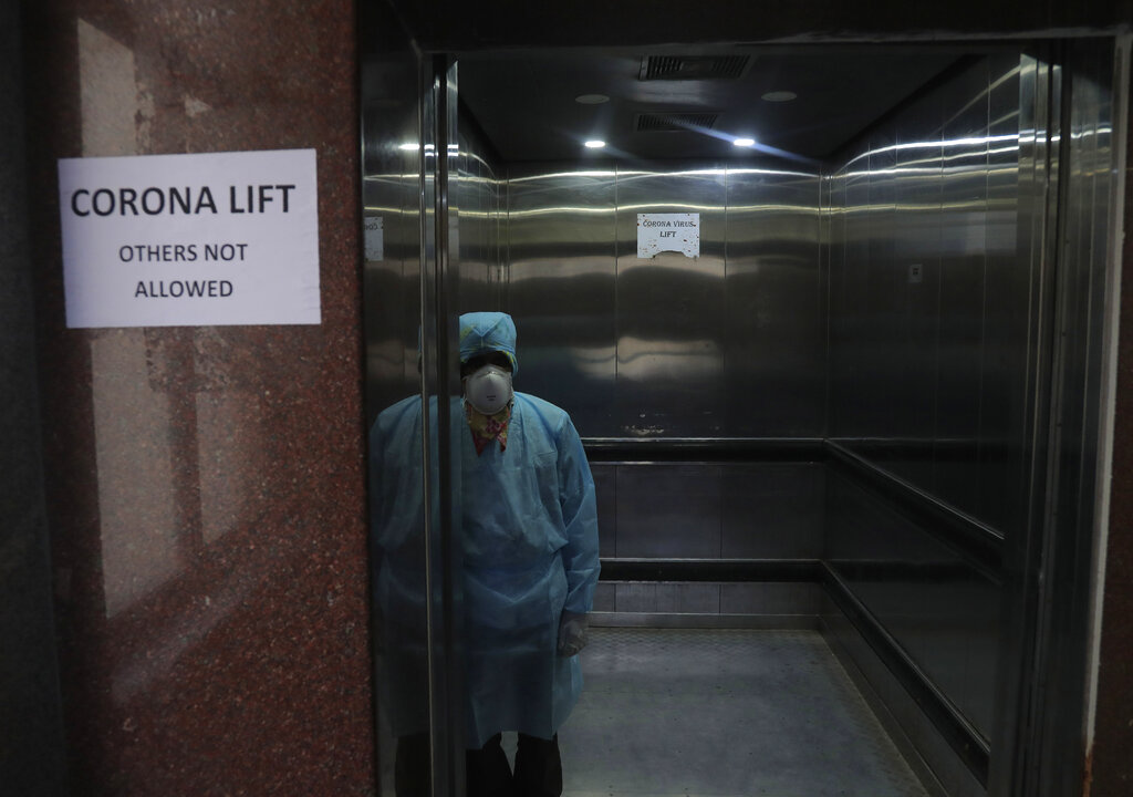 A lift operator stands inside a dedicated lift for people suspected to be infected with the new corona virus at the Government Gandhi Hospital in Hyderabad, on Monday, March 2, 2020. Coronavirus has spread to more than 60 countries, and more than 3,000 people have died from the COVID-19