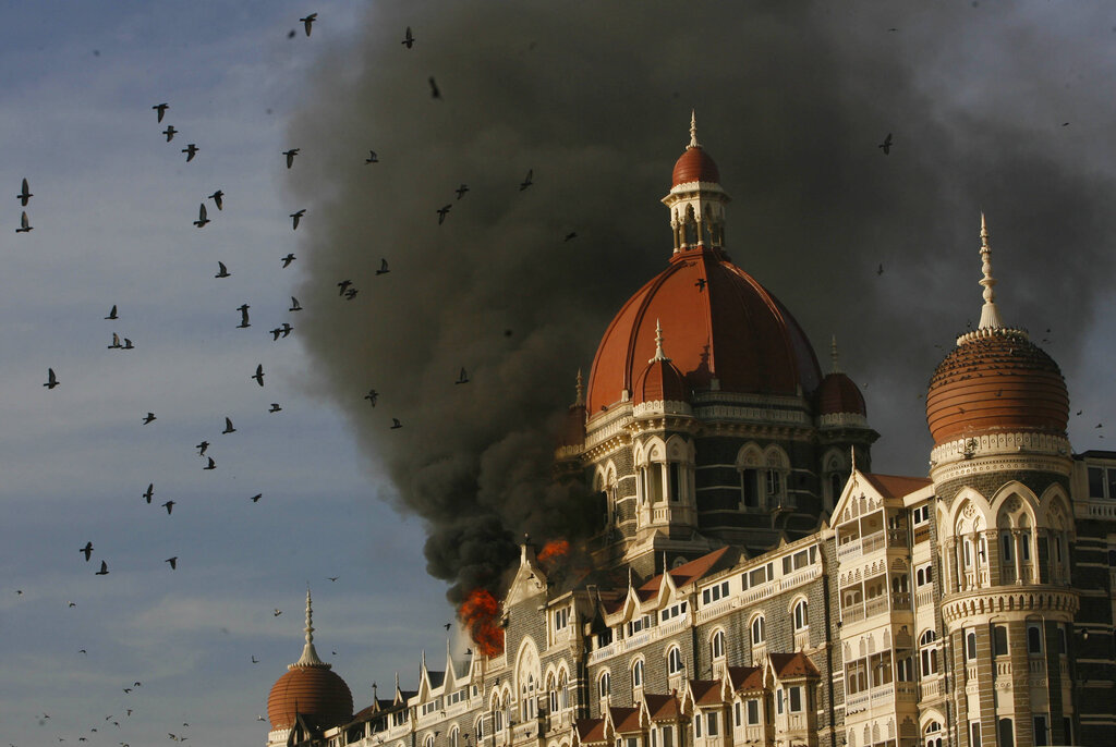 In this Nov. 27, 2008, file photo, pigeons fly as the Taj Hotel continues to burn from an attack that killed multiple people in Mumbai, India. Tahawwur Rana, a Pakistani-born Canadian, was convicted of a crime related to the Mumbai killings.