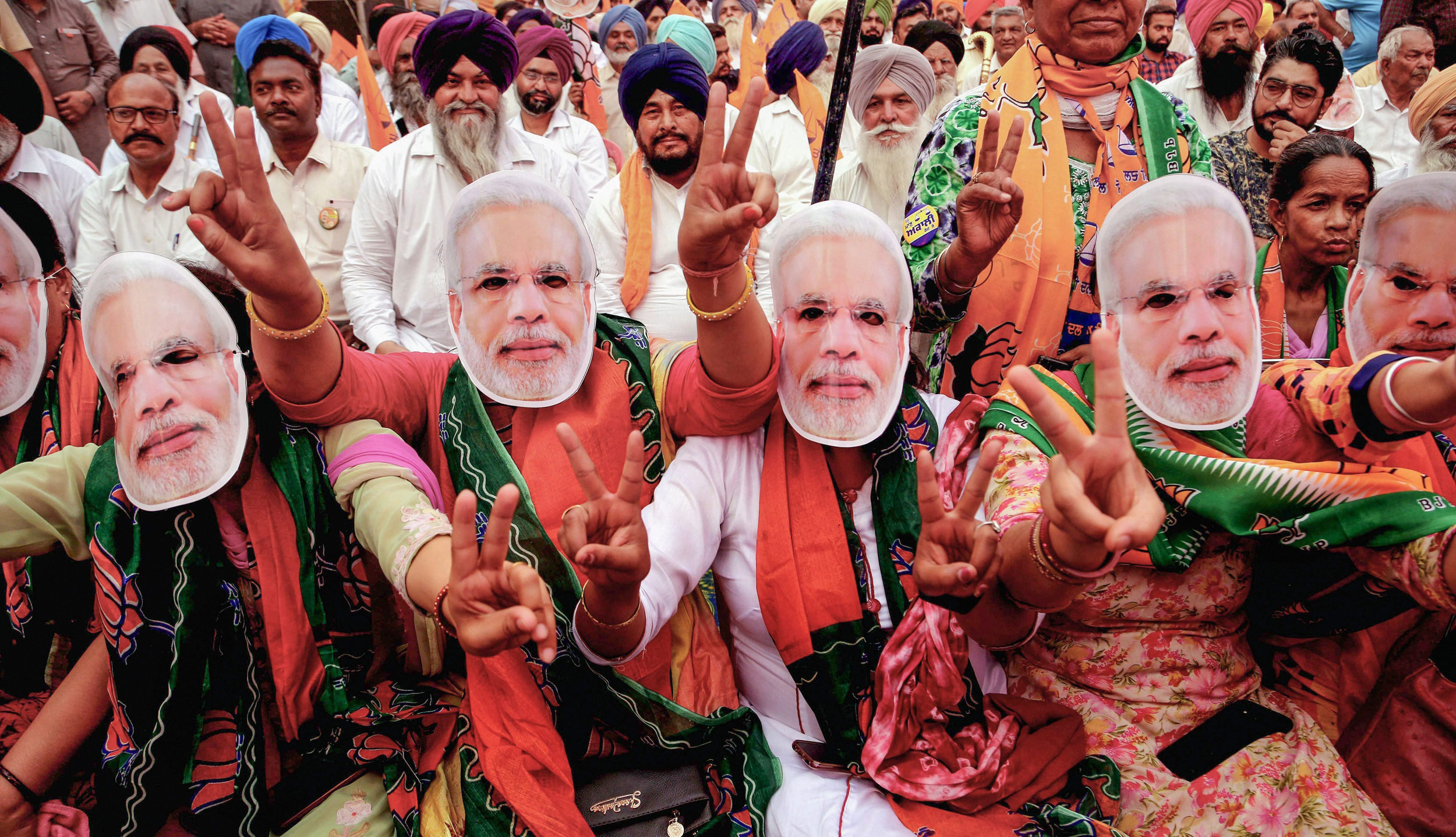 BJP supporters wear masks of Prime Minister Narendra Modi during an election rally for the last phase of the Lok Sabha polls, in Patiala, on May 16, 2019.