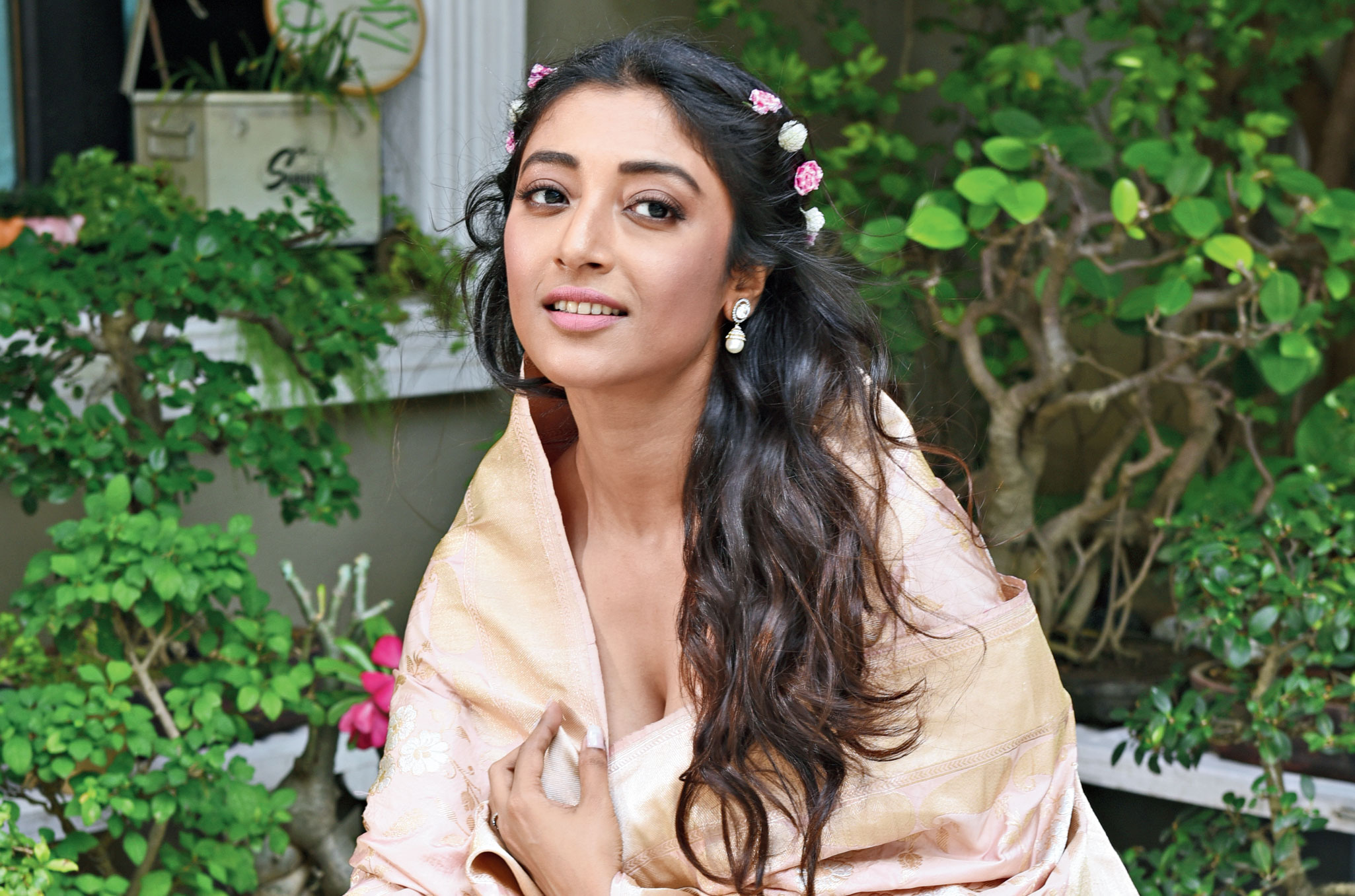 """Paoli Dam was a picture of feminine elegance and soft charm in blush pink. """"The skirt is in Chanderi silk and the dupatta is a Benarasi handwoven one,"""" said Pinki Sinha. Roses, """"a symbol of love"""" and woven silver and gold foliage added to the mellow serenity. """"It's all about a little happiness, love and romance in the air. This is great for the day,"""" added Pinki. For Paoli, this was a """"fairy-tale look"""". """"It's a very mishti rong. You can wear it for Mehndi, cocktail and reception. It's got a lehnga feel. I loved the dupatta,"""" said Paoli. Soft pink and gold shimmer, nude pink lips, brown liner on the eyes, soft pink blush and wavy hair done up with real flowers up the princess-romance quotient."""