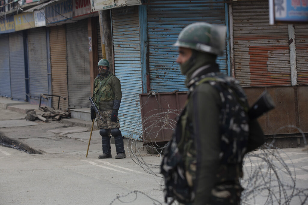 Indian paramilitary soldiers stand guard in a closed market area during a strike on the death anniversary of separatist leader Maqbool Bhat in central Srinagar, Kashmir on Tuesday, Feb. 11, 2020.