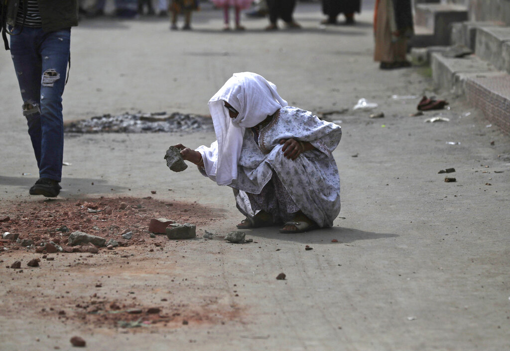 An elderly Kashmiri woman breaks stones to hand out to protestors for throwing at security personnel in Srinagar, Kashmir, on Friday, Aug. 30, 2019