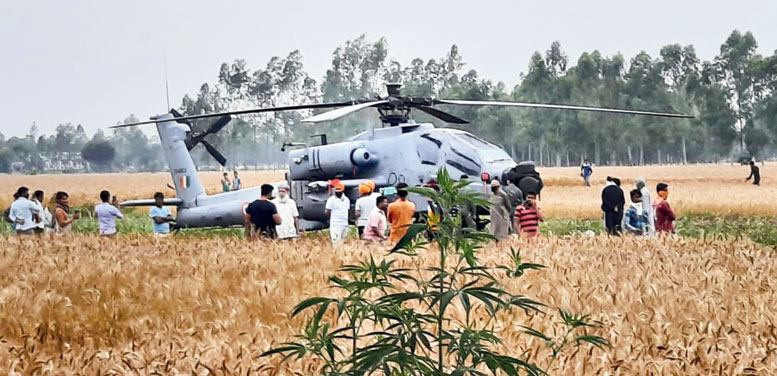 Residents stand near the Apache helicopter that made an emergency landing in the fields of Budhawar village in Hoshiarpur district of Punjab on Friday.
