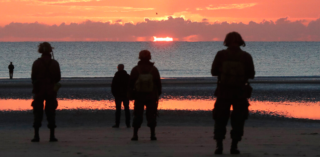 World War II re-enactors stand on Omaha Beach, in Normandy, France, at dawn on Thursday, June 6, 2019 during commemorations of the 75th anniversary of D-Day.
