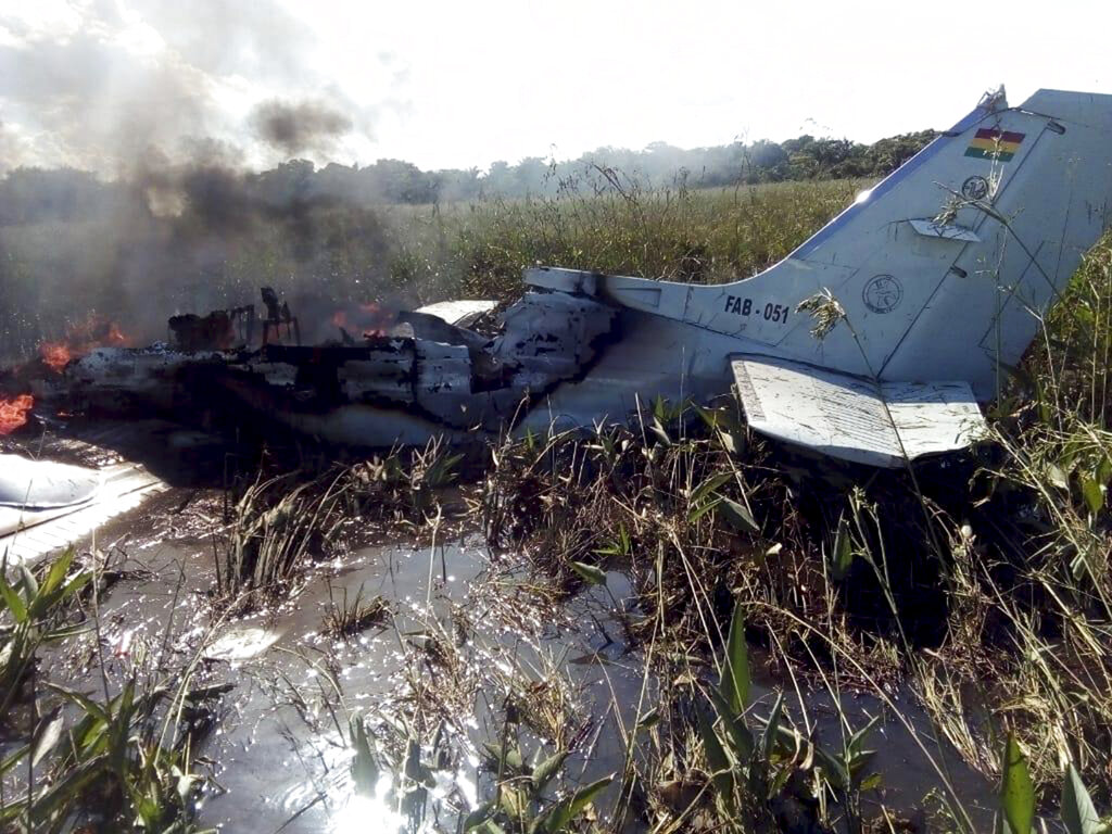 The remains of an aircraft from the Bolivian Air Force burn after crashing near Trinidad, Bolivia, Saturday, May 2, 2020. The plane, flying a humanitarian mission, crashed minutes after takeoff in the Amazonian region, killing all six occupants, including four Spaniards who were being ferried to catch a flight to their homeland, the Defense Ministry said Saturday.