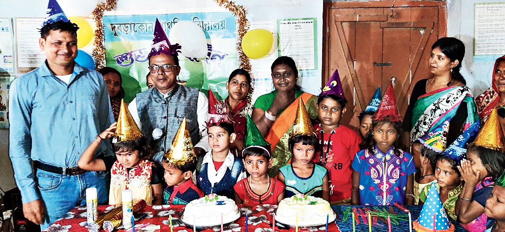 A teacher (extreme left) and the headmaster of Dubrakone primary school in Onda, Bankura, with children and their guardians at the birthday celebration on Saturday