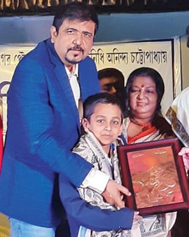 Minister Sujit Bose felicitates Pratyay at Laban Hrad Mancha in BD Block on Sunday.