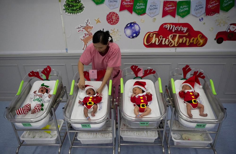 A nurse adjusts the outfits of newborn babies dressed in Santa costumes on Christmas eve in Bangkok on December 24