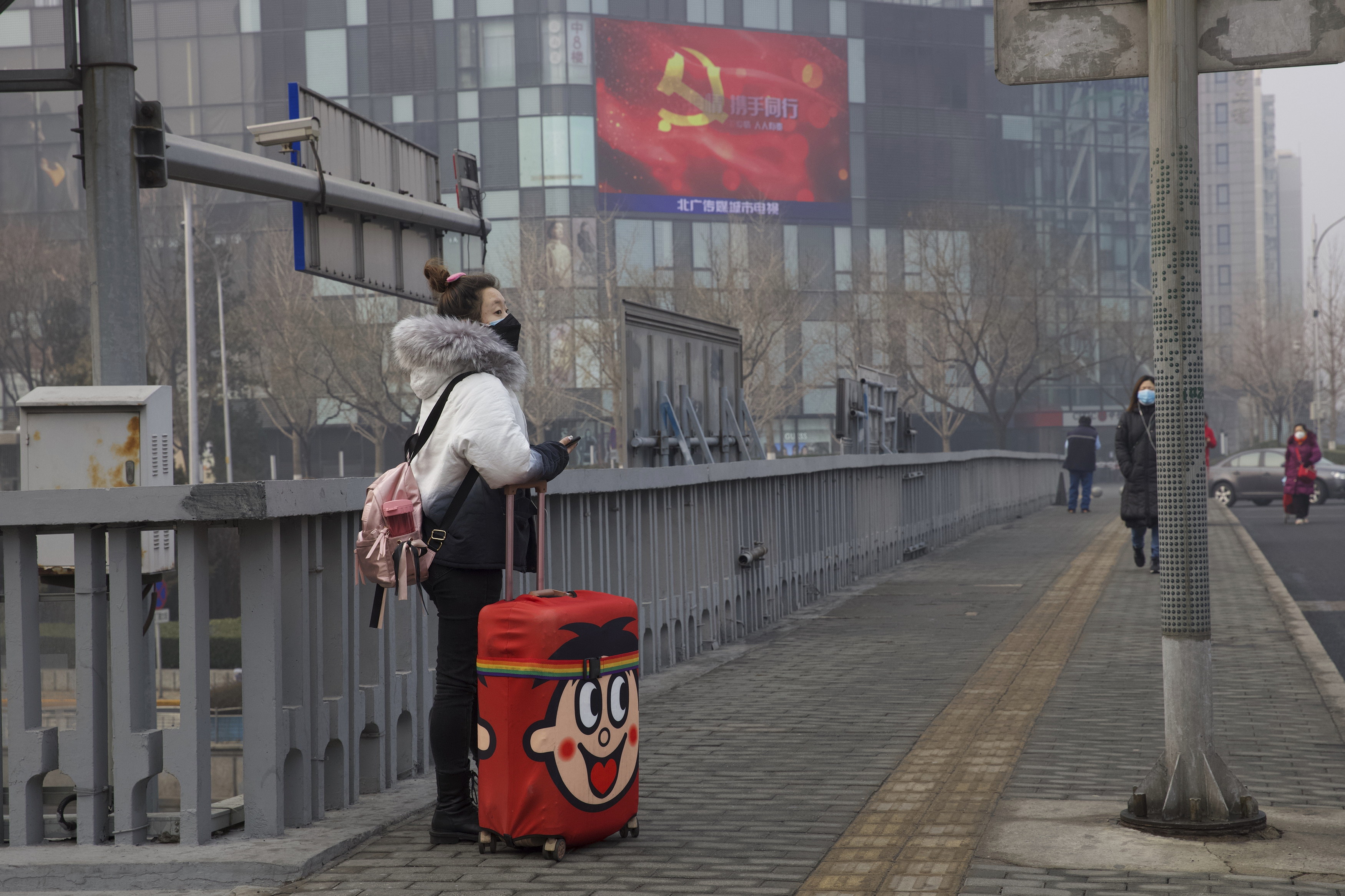 A traveler stands on a bridge near a display showing government propaganda in the fight against the COVID-19 viral illness in Beijing, China  on Thursday
