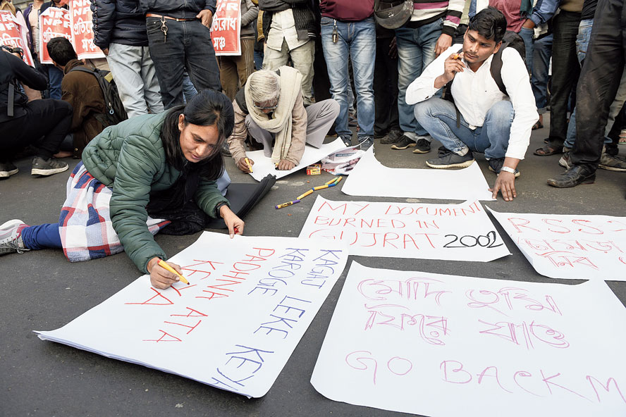 Schoolteacher Kazi Ruma Quntum (left) writes a poster on VIP Road, near the Kaikhali crossing, on Saturday afternoon.