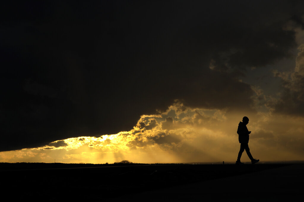 Aliyah Mosby is silhouetted against the sunset as she walks at the Liberty Memorial Thursday, March 19, 2020, in Kansas City, Missouri. Mosby was taking advantage of warm weather on the first day of spring to get some fresh air as most of the community isolates to limit the spread of the coronavirus.