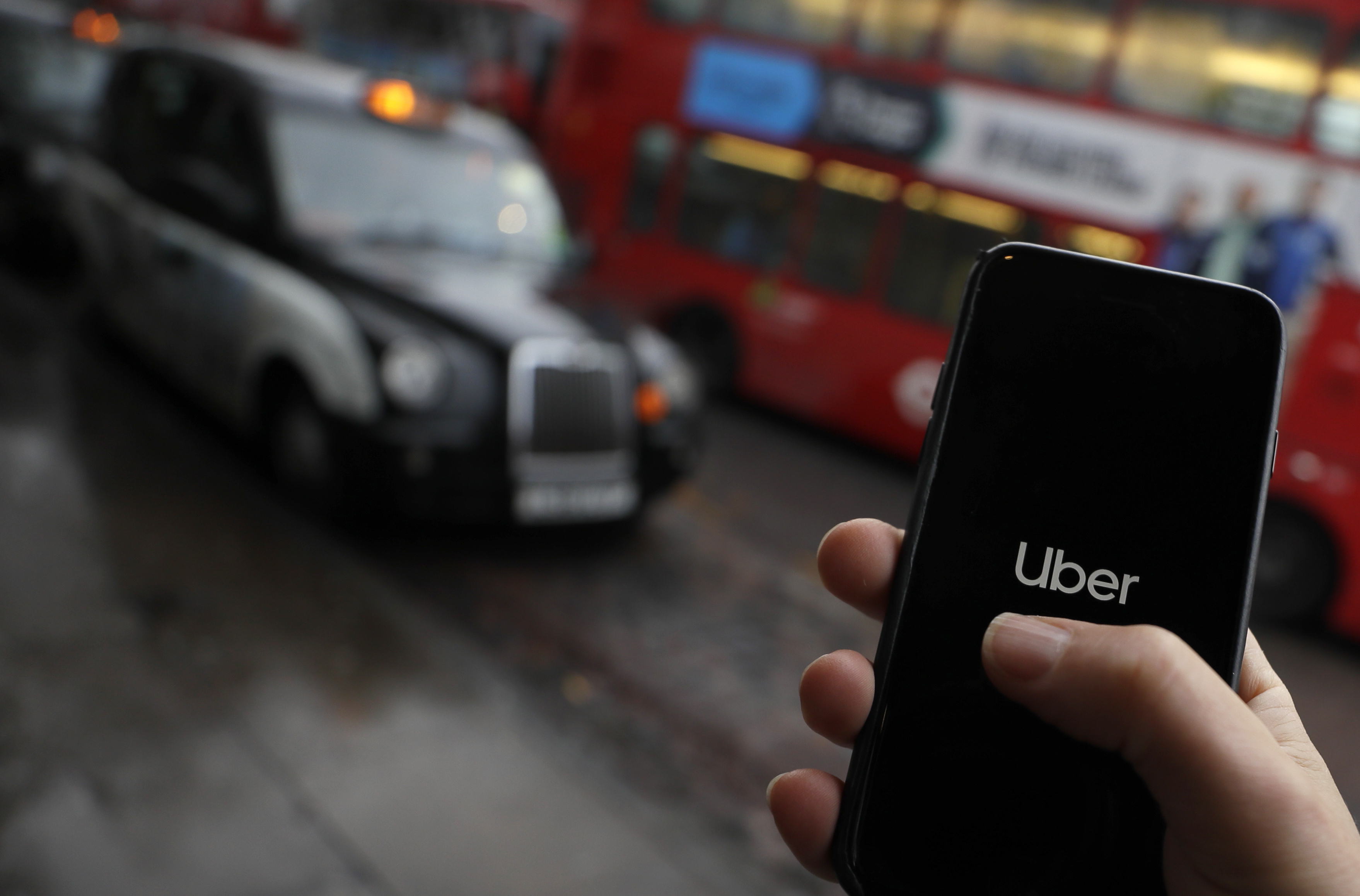In this posed picture, the Uber app is opened on a mobile phone, backdropped by other transport services in London, Monday, November 25, 2019