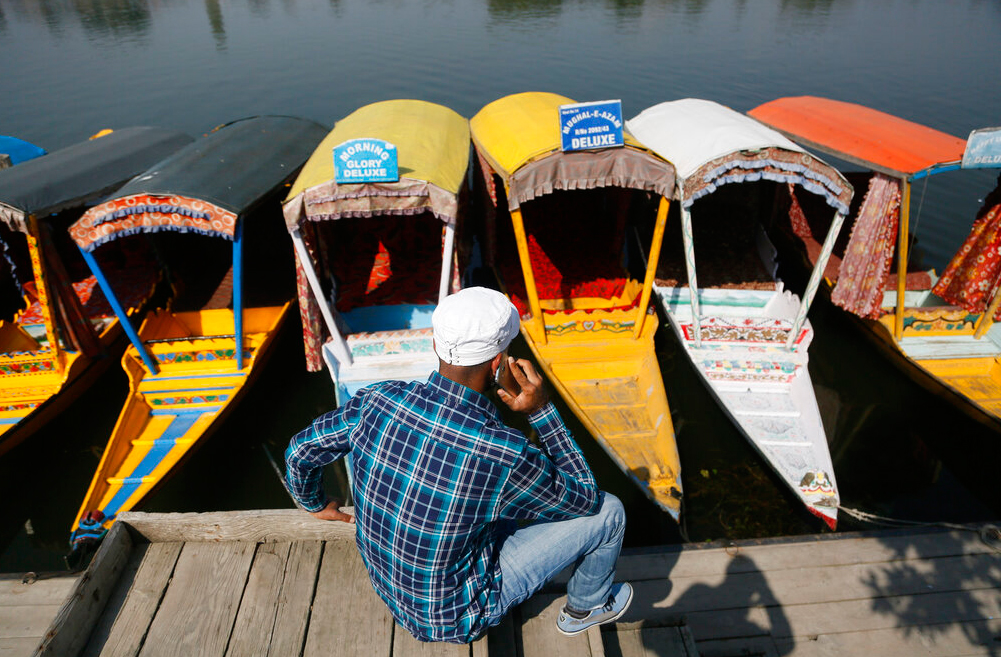 A Kashmiri boatman talks on his cellphone as he sits on the banks of the Dal Lake in Srinagar on Monday, October 14, 2019.