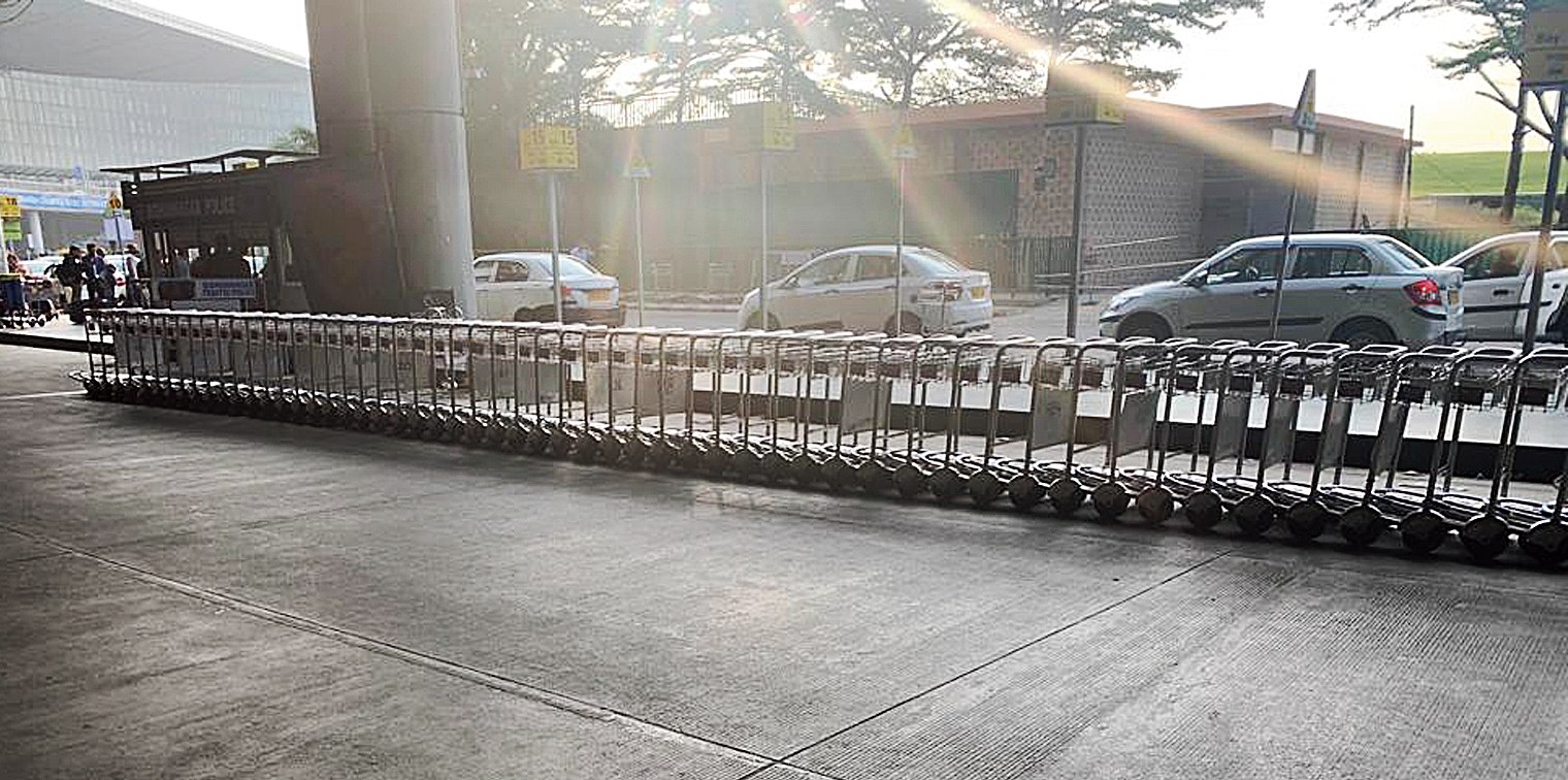 A long row of trolleys block a lane in front of the airport terminal at the arrival level