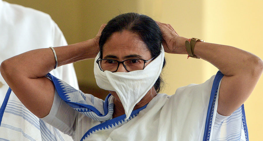 West Bengal Chief Minister Mamata Banerjee covers her mouth with a piece of cloth during a press conference on coronavirus, at Nabanna