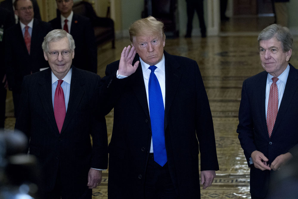 President Donald Trump accompanied by Senate Majority Leader Mitch McConnell of, left, and Senator Roy Blunt, right, arrives for a Senate Republican policy lunch on Capitol Hill in Washington, Tuesday, March 26, 2019.