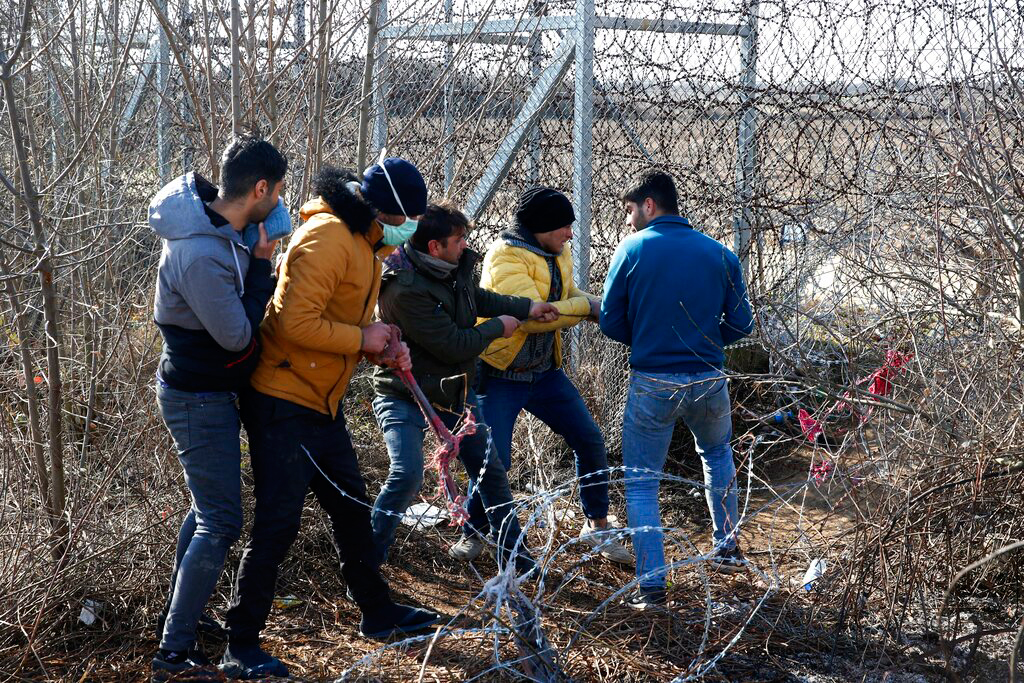 Migrants try to cut the fence in Edirne, Turkey, on March 2