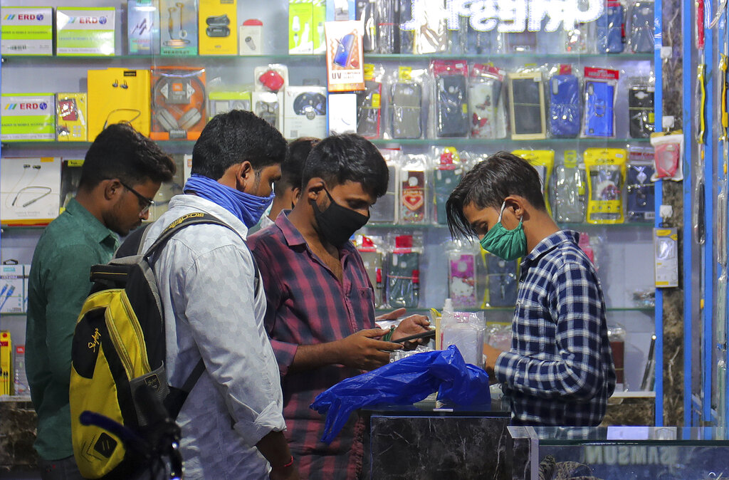 People wearing face masks shop for accessories at a mobile shop in Hyderabad, Thursday, June 25, 2020
