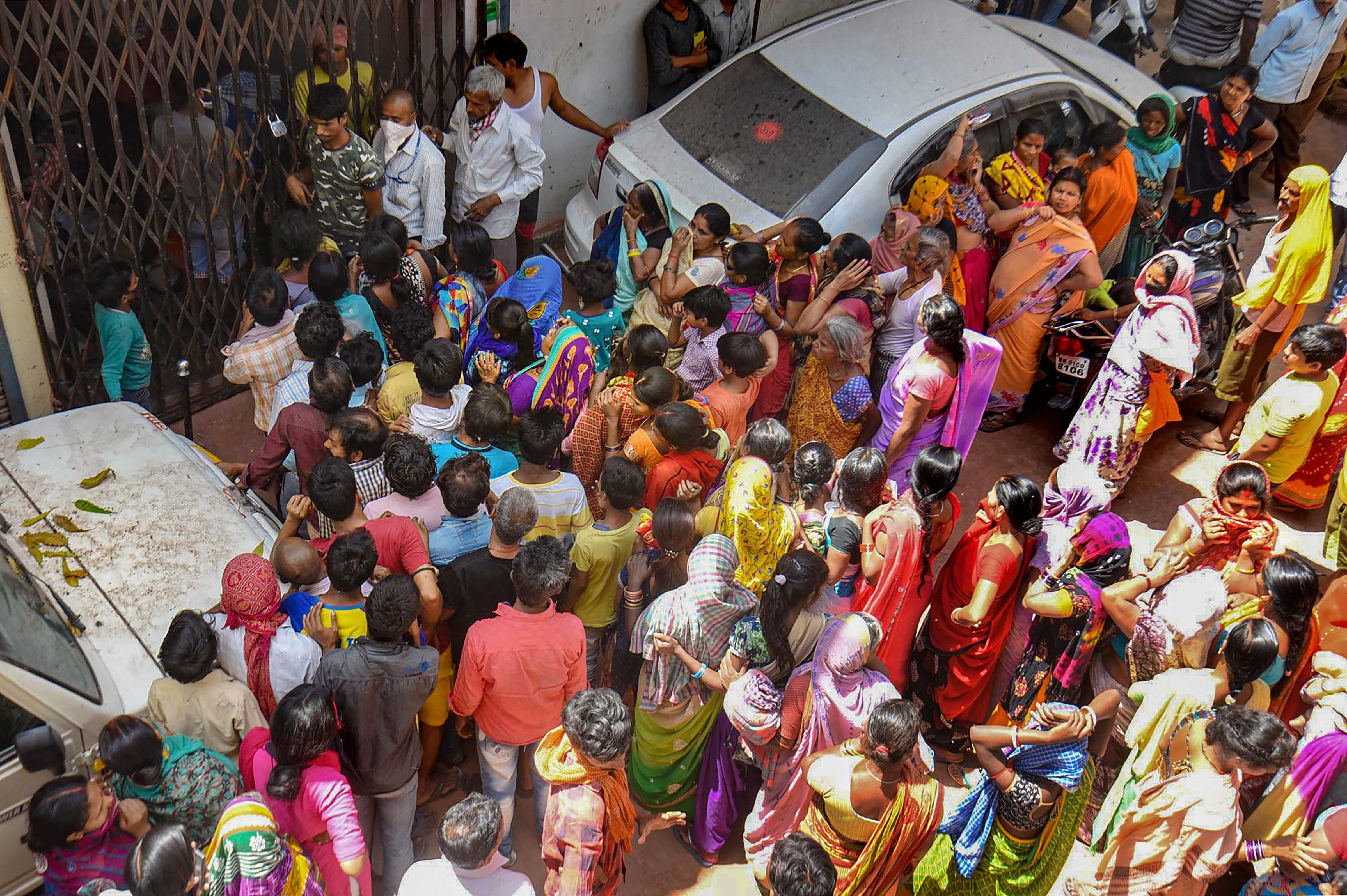 People gather outside ration distribution center to collect food items during a nationwide lockdown in the wake of the coronavirus pandemic in Patna