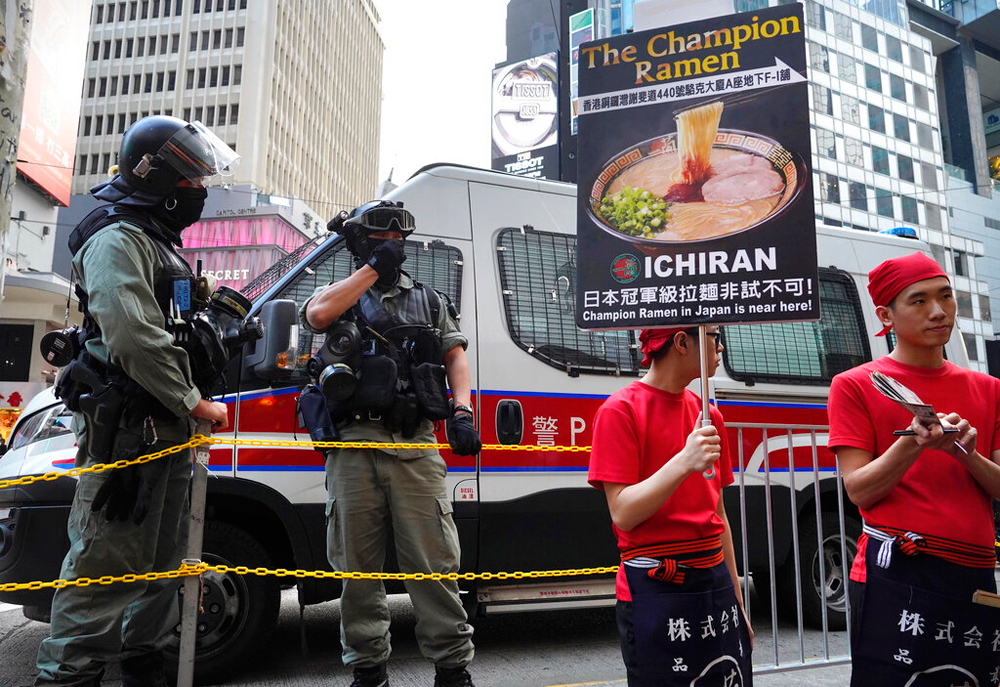 Riot police stand near workers advertising a noodle shop in Hong Kong on December 26