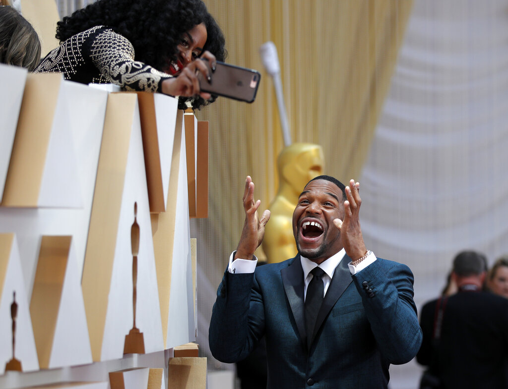 Michael Strahan takes a selfie with a guest as he arrives at the Oscars on Sunday, February 9, 2020, at the Dolby Theatre in Los Angeles