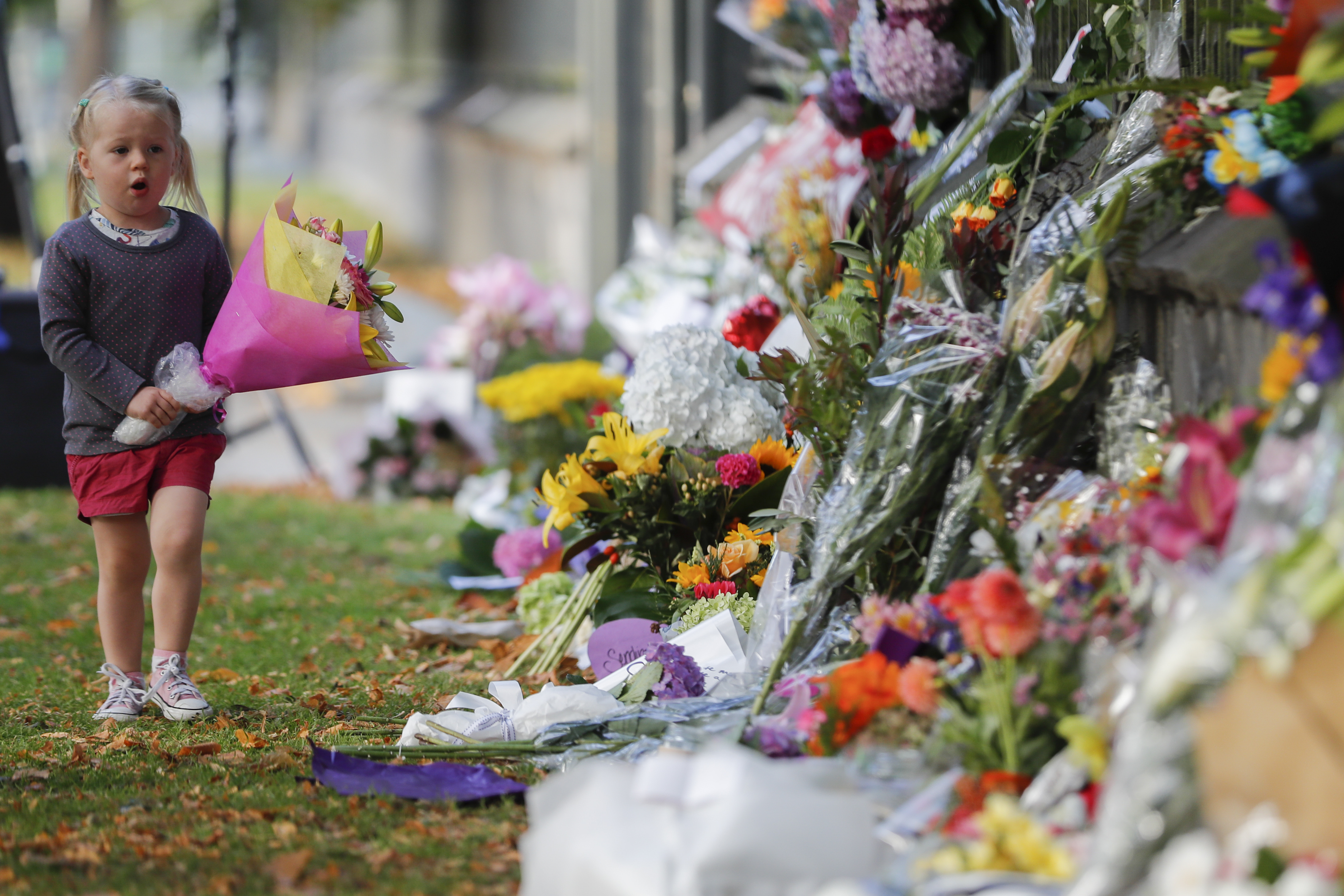 A child carries flowers to a memorial wall following the mosque shootings in Christchurch, New Zealand.