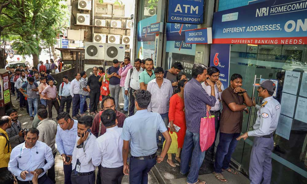 Customers gather outside a Thane branch of Yes Bank to withdraw money on Friday
