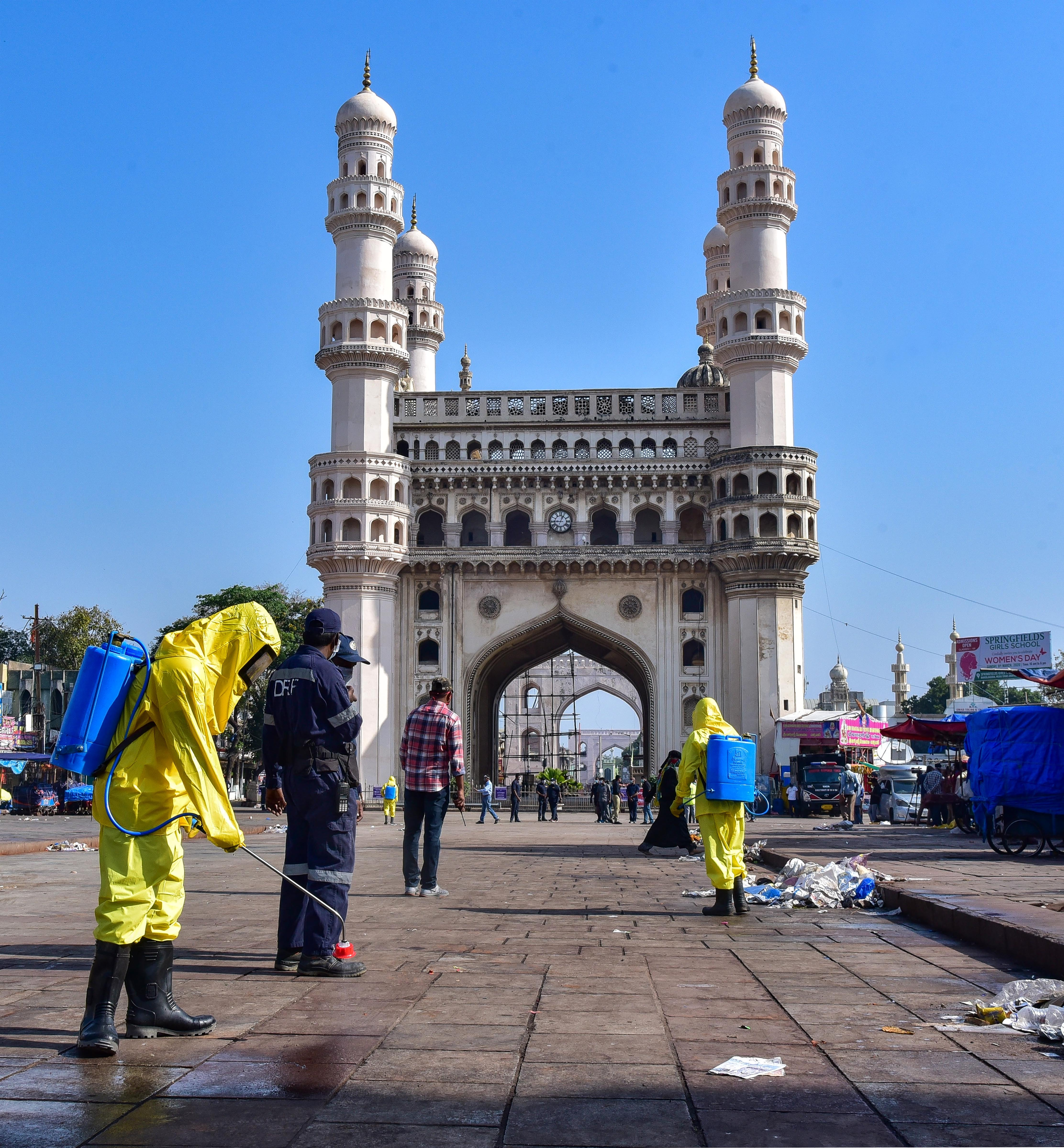 Workers disinfectant an area near the historic Charminar during Janata curfew in the wake of coronavirus pandemic, in Hyderabad, Sunday, March 22, 2020