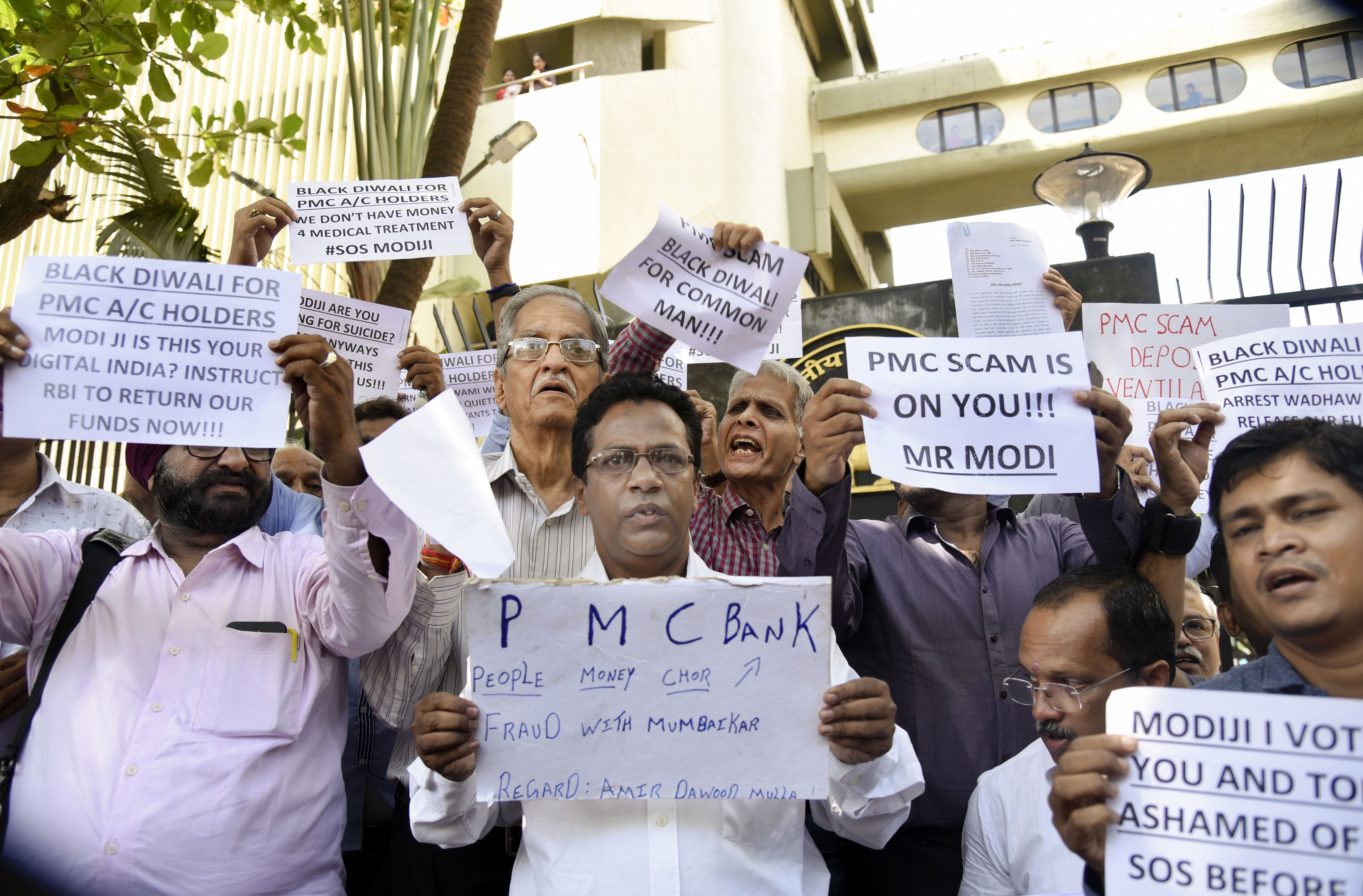 Depositors of Punjab and Maharashtra Cooperative (PMC) Bank display placards during a protest over the banks crisis, outside the Reserve Bank of India building, in Mumbai, Tuesday, October 1, 2019