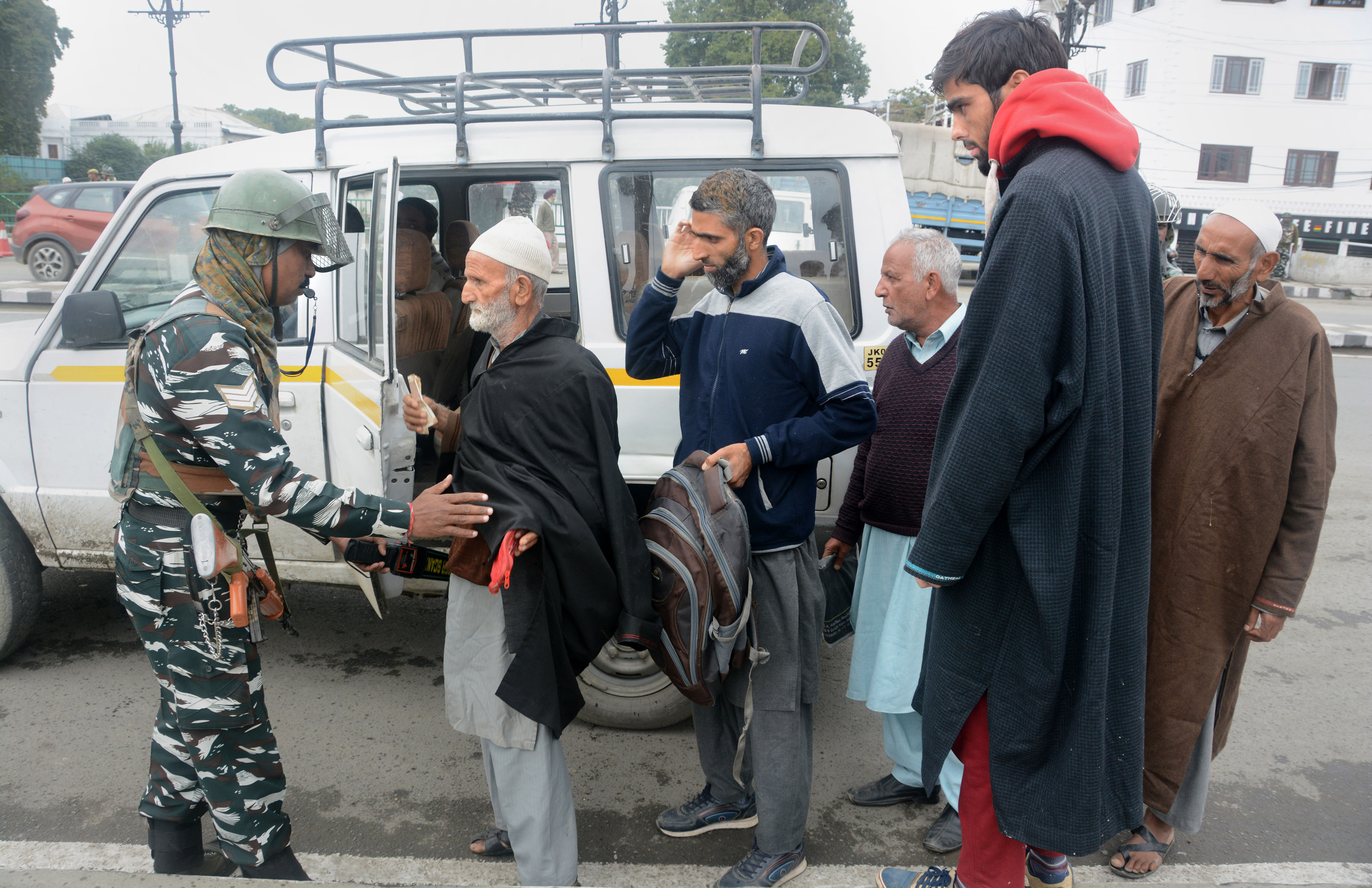 In this file picture from Monday, October 7, 2019, a security person can be seen frisking passengers of a private vehicle during a high alert, in Srinagar. Security has been beefed up in the city after a grenade attack injured seven people on Sunday, October 13, 2019
