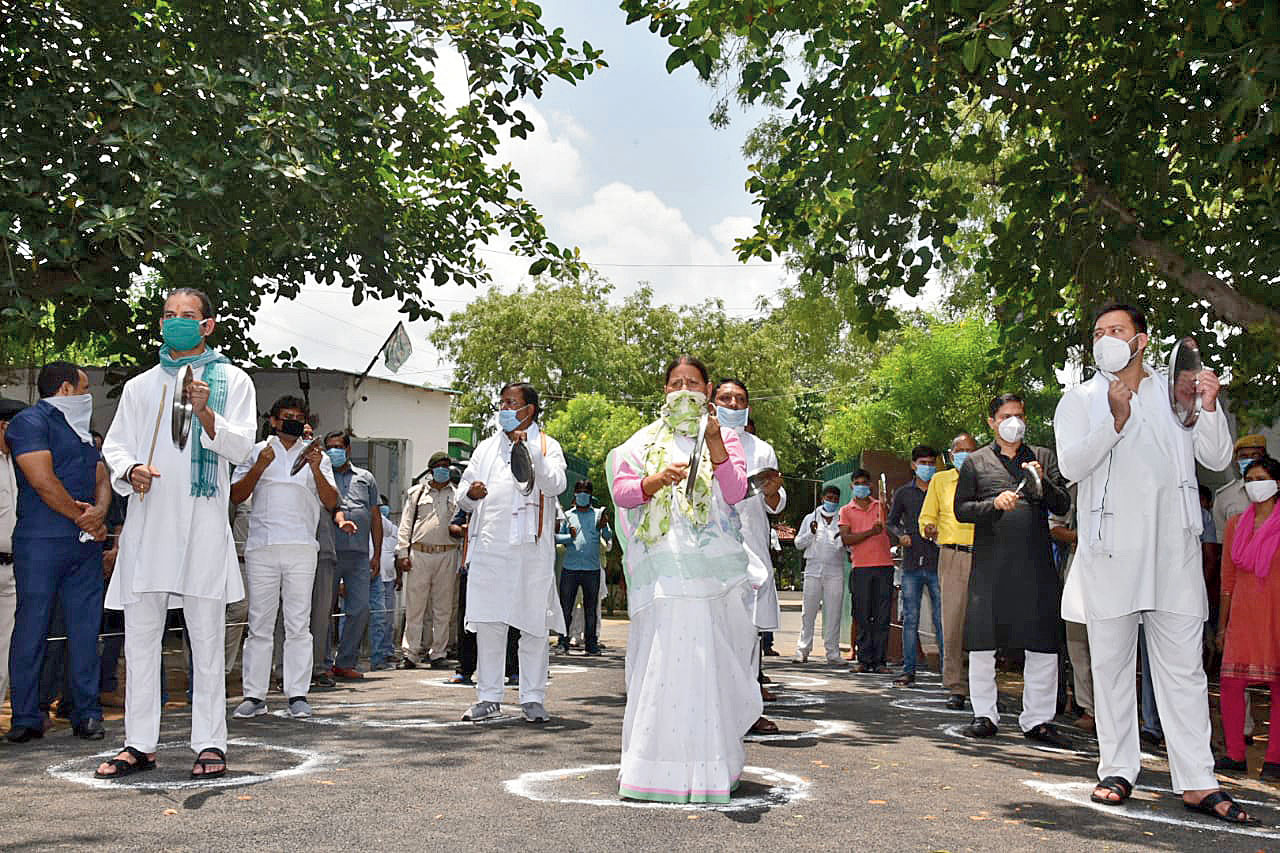 RJD leaders Rabri Devi, Tejashwi Prasad Yadav, Tej Pratap Yadav and others clank untensils outside Rabri's residence in Patna on Sunday to protest Amit Shah's virtual rally.