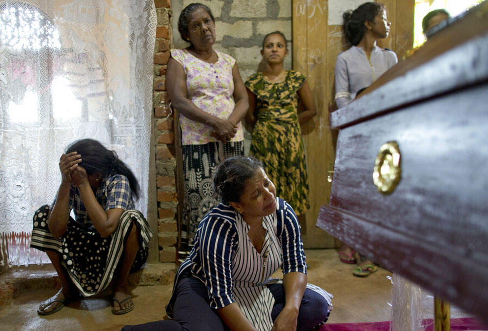 Relatives on Monday weep near the coffin with the remains of 12-year-old Sneha Savindi, who was a victim of the Easter bombings at St Sebastian Church in Negombo, Sri Lanka