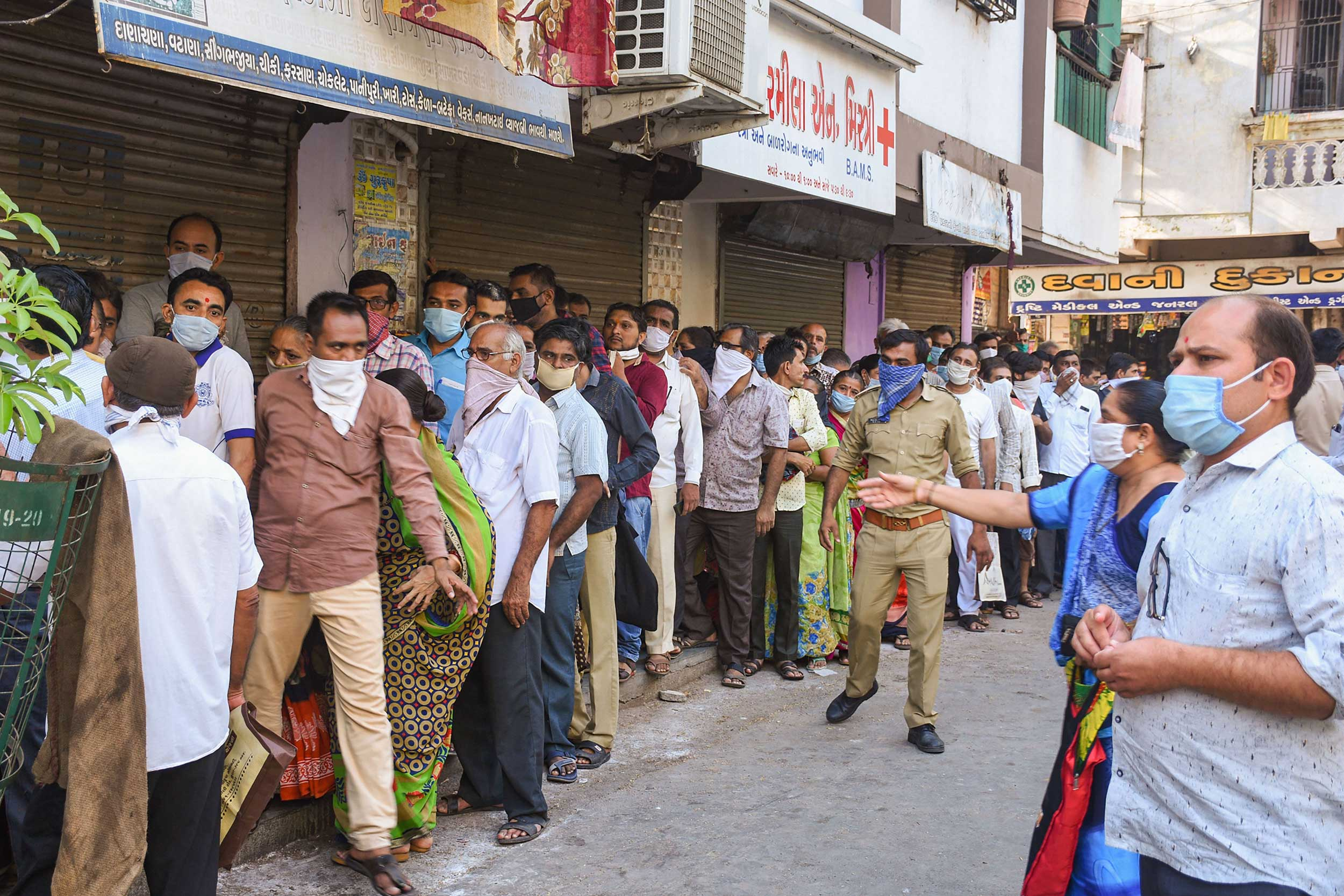 IGNORE SOCIAL DISTANCING: People stand in a queue to collect ration during the nationwide lockdown in Surat on Tuesday.