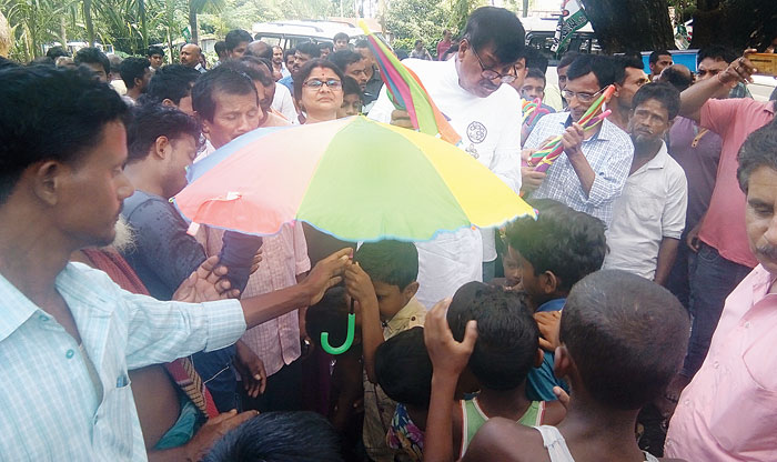 Rabindranath Ghosh hands out an umbrella as part of the Didi Ke Bolo campaign