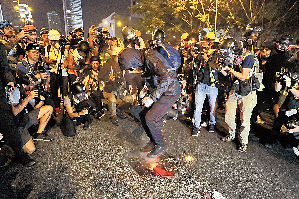 A protester stomps on a burning Chinese flag in Hong Kong on Saturday.